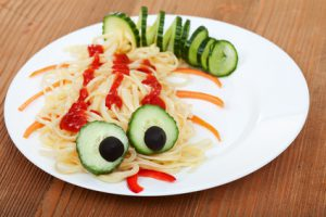 Creative pasta dish with cucumber creature - on wooden table